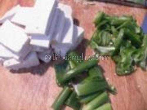 豆腐买来控水晾干一下,即干豆腐最好,切成约5公分长的片。葱切段,辣椒切碎即可,还有姜片未拍。