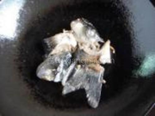 锅中热油,放入姜丝炸香,再放入鱼头,煎至表面金黄。