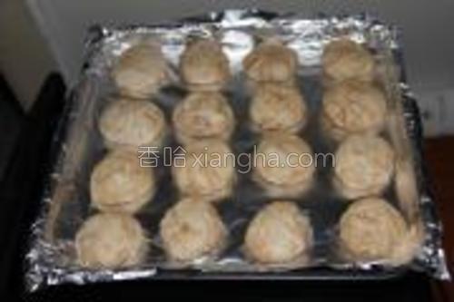 调好的麻酱均匀抹在大面饼上,从一边卷起,卷成卷状后,切成均匀的十六段,将每个段搓成一个小面饼,放入铺好锡纸的烤盘。