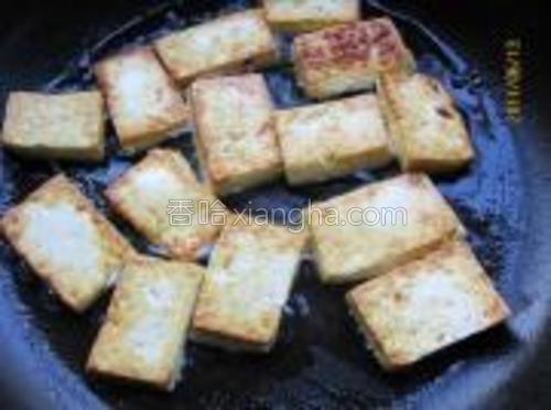 豆腐切成大片入油锅中煎至两面焦黄。