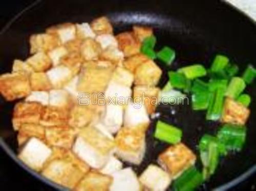把煎好的豆腐推在一边下入葱段煸香。