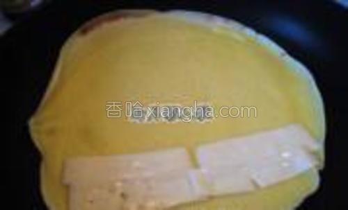 奶酪片切成几片,放在边上。饼继续煎30秒,或者待奶酪片稍微融化。