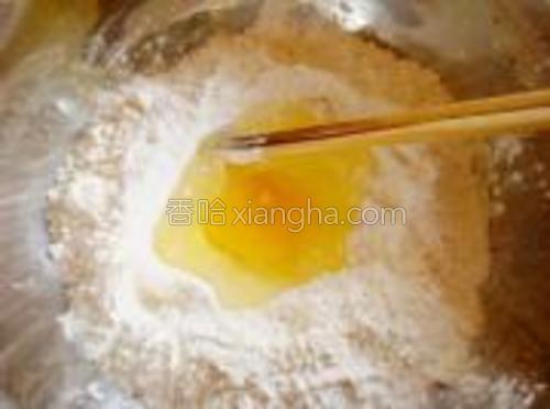 面粉中放入1个鸡蛋和适量水。