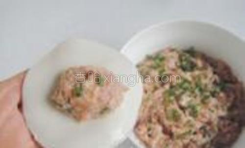 取一块饺子皮,包入适量肉馅,用食指在饺子皮的边缘抹上少许请水。(因为买的饺子皮上面比较多干粉,这样便于包)