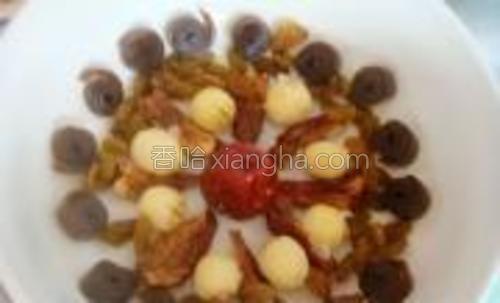 把红枣、莲子、葡萄干、桂圆肉、果丹皮摆到碗底中。
