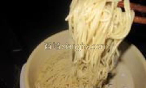 面条吹得差不多了,就拿一个木筷子来抖散面条,边抖面条的同时边加油,防止面条间的粘连,一定是边抖边加油,看的粘住了就多加点油可以用菜油也可以用芝麻油