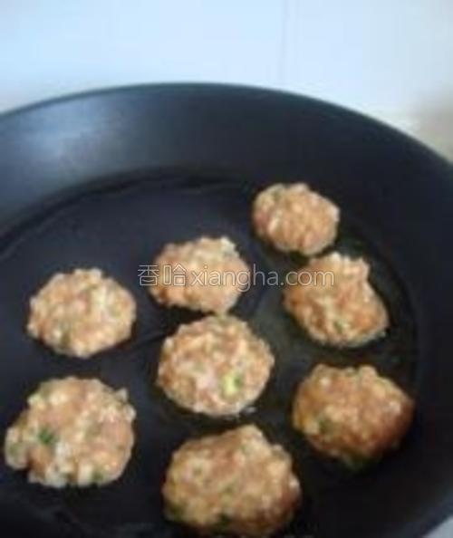 用手的虎口挤成丸子,勺子顺势钥出来,放在有橄榄油的平底煎锅中。