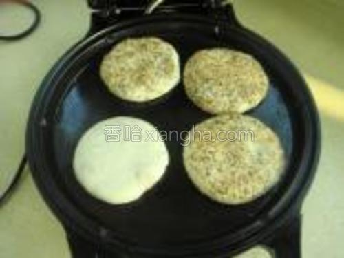 饼铛遇热刷油,将饼胚放入开始煎。